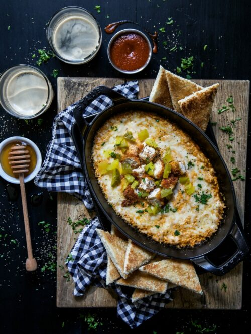 hot chicken dip with honey toasts on a table