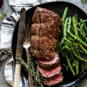 roasted beef tenderloin on a plate with green beans