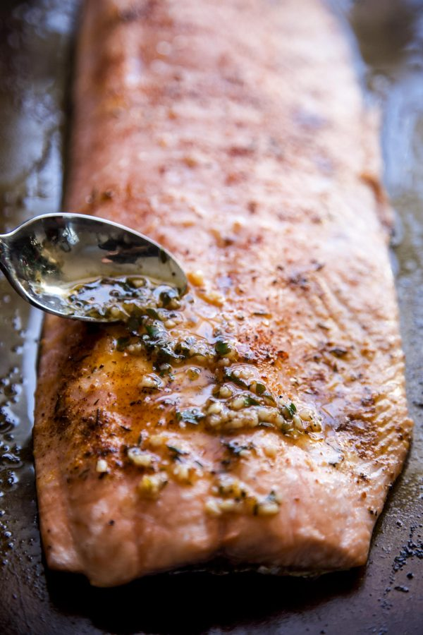 garlic and butter being put on salmon