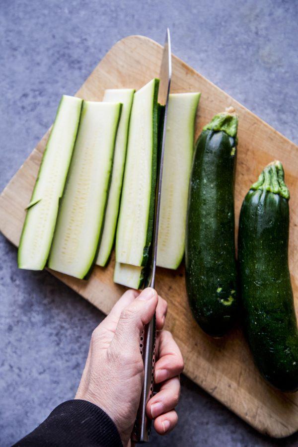 zucchini being sliced on a cutting board