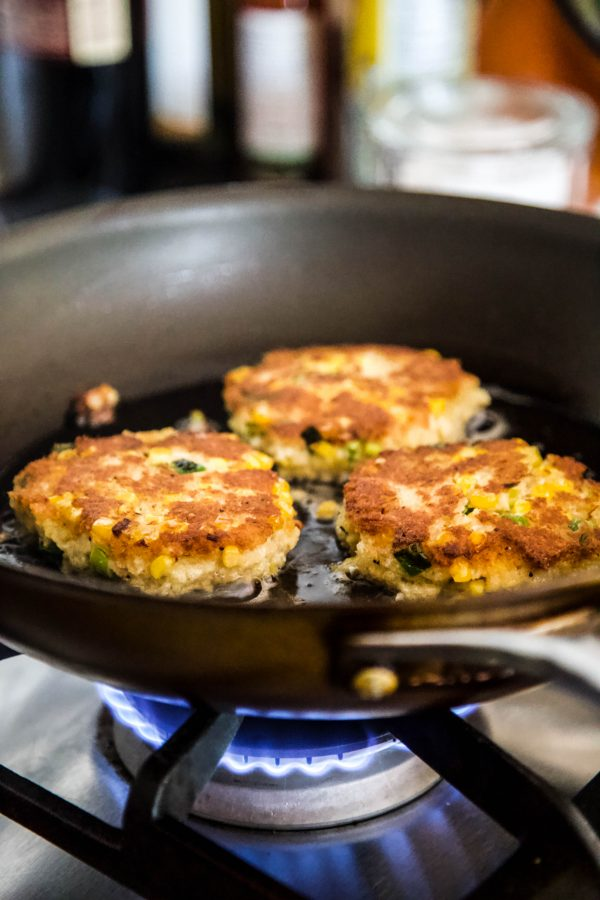 crab cakes cooking in a skillet