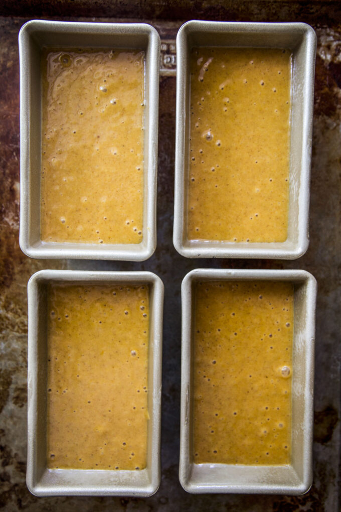four loaf pans full of pumpkin bread batter